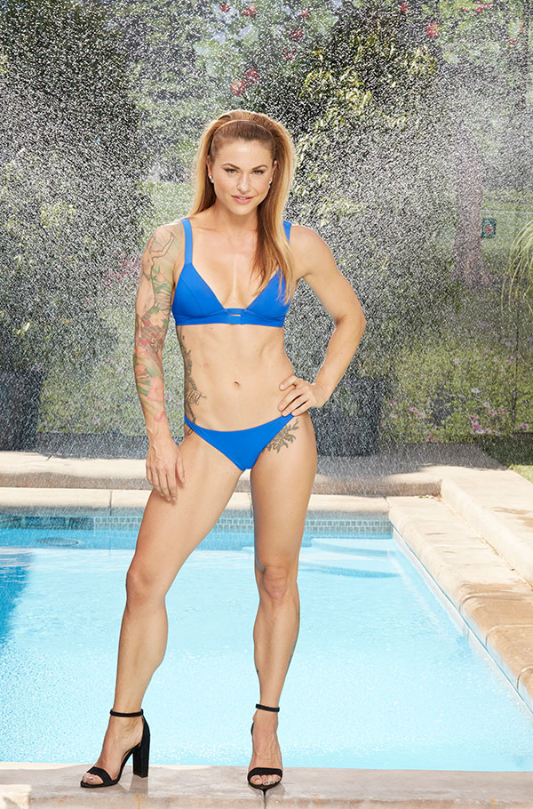 Christmas Abbott shows off her body art in a skimpy blue bikini.